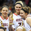 Sisters, from left, Marnie, Carlie and Maddie Wagner hug as they hold their all tournament team trophies Saturday at Williams Arena. Photo by Pat Christman