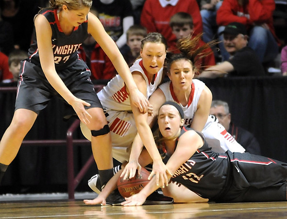 Kenyon-Wanamingo's Megan Quam (32) and Meg Clark (12) battle for a loose ball with NRHEG's Paige Overgaard and Hannah Lundberg during the first half of the Class AA state championship game Saturday at Williams Arena. Photo by Pat Christman