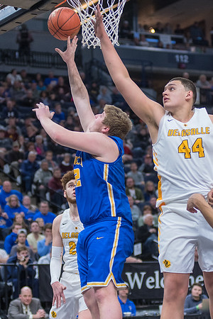 Matt Olsem (left) of Waseca goes in for a reverse layup against De La Salle's Jalen Travis in the Class AAA championship game. The Bluejays lost 63-56 to the Islanders. Photo by Jackson Forderer