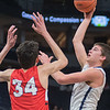 St. Peter's Wyatt Olson takes a hook shot over Minnehaha Academy's Chet Holmgren in the first half of Wednesday's quarterfinal game of the Class AA Boys State Basketball Tournament at Target Center in Minneapolis. The Saints fell to the top seed 78-47. Photo by Jackson Forderer