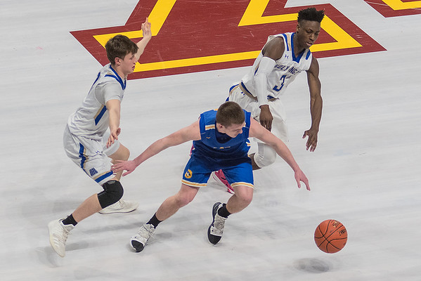 Ryan Dufault (center) of Waseca goes after a loose ball against Academy of Holy Angels Charles Johnson and Nate Kesti in the second half of Wednesday's game. Waseca won 82-62 to advance in the Class AAA Boys Basketball State Tournament. Photo by Jackson Forderer