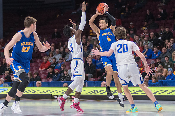 Waseca's Malik Willingham looks to the pass the ball to a teammate while being defended by Academy of Holy Angels' Thor Holien (20) and Charles Johnson in Wednesday's quarterfinal game. Photo by Jackson Forderer