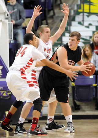 Mankato West's Braedan Myers (34) and Jake Dale surround Marshall's Aaron Mathiowetz during the first half of their Section 2AAA semifinal game Saturday at Bresnan Arena.