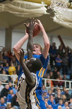 Uhana Ochan of Mankato East tries to block a shot by Jake Guse of Waseca in the first half of the Section 2AAA semifinal game played in St. Peter on Saturday. Waseca won in overtime 69-66 to advance to the section final game against Marshall. Photo by Jackson Forderer
