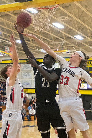 Mankato East's Uhana Ochan goes up for a layup against Worthington's Stewart Merrigan (33) and Logan Huisman in the second half of Tuesday's Section 2AA quarterfinal game. Photo by Jackson Forderer