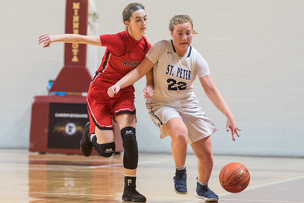 St. Peter's Jacey Welp dribbles up the court while being pressured by Minnehaha Academy's Kate Pryor in the first half of the Class AA quarterfinal game played at the Pavilion on Wednesday. Photo by Jackson Forderer