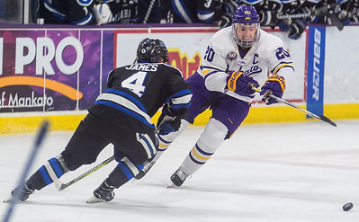Minnesota State's Marc Michaelis goes after the puck in the offensive zone while being defended by University of Alabama-Huntsville's Connor James. Photo by Jackson Forderer
