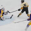 Mankato East/Loyola's Sam Schulz (16) watches his shot go up and over the glove of Rochester Lourdes goaltender Ryan Smith for a goal in the second period of Wednesday's Section 1A championship game. East opened up their offense by scoring three goals in the second period. Photo by Jackson Forderer