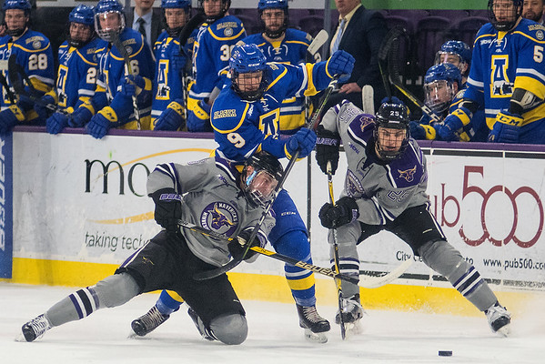 Minnesota State's Parker Tuomie (left) and Riese Zmolek (right) go after a loose puck against University of Alaska Fairbanks' Justin Young in the second period of Friday's playoff game played at the Verizon Center. Photo by Jackson Forderer