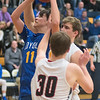 Mankato Loyola's Isiah Godfrey (11) puts up a shot against Alden-Conger's Alex Cummings (30) and Gavin Steele in the second half of Thursday's game as the Crusaders pulled away and won 73-34 to advance in the Section 2A tournament. Photo by Jackson Forderer