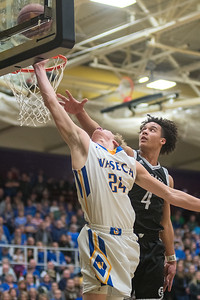 Waseca's Jack Vetsch gets a layup in underneath a block attempt from Mankato East's Damani Hayes in the first half of Thursday's Section 2AAA championship game. The Cougars withstood a tenacious comeback effort by Waseca and won 78-70. Photo by Jackson Forderer