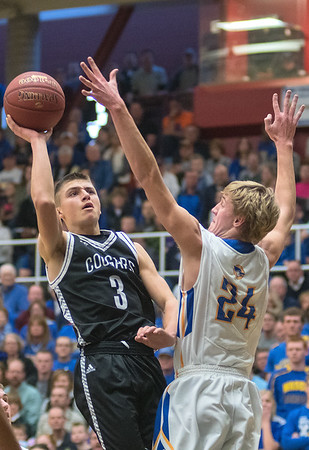 Mankato East's Jax Madson puts up a shot over Waseca's Jack Vetswch (24) in the first half of Thursday's Section 2AAA championship game. Photo by Jackson Forderer