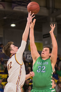 Maple River's Sam Bennett (32) has his shot blocked by Jordan's Andrew Niebuhr in the first half of Friday's Section 2AA championship game played at Bresnan Arena. Niebuhr's length caused trouble for the Eagles offense. Photo by Jackson Forderer