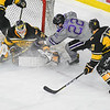 Minnesota State's Dallas Gerards (22) and Michigan Tech goalie Devin Kero scramble for the puck in a spray of ice, neither of them aware that the puck sailed to the right of Michigan Tech's Justin Misiak (17) in a game played on March 9 at the Verizon Center. Photo by Jackson Forderer