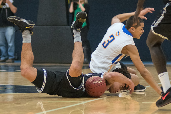 Mankato East's Damani Hayes gets fouled by Waseca's Kyreese Willingham (3) while diving for a loose ball in the second half of Thursday's Section 2AAA championship game played in St. Peter. Photo by Jackson Forderer