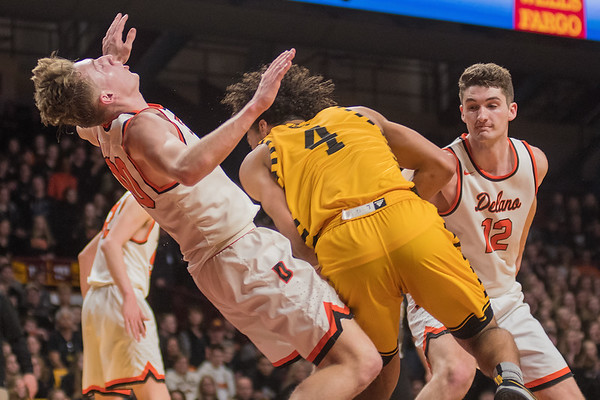 Delano's Calvin Wishart (left) takes a charge from Mankato East's Damani Hayes. It would be Hayes' fifth foul in the game. Photo by Jackson Forderer