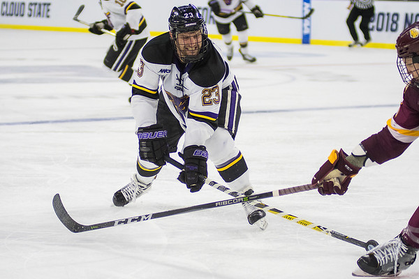 Minnesota State's Nicolas Rivera pokes the puck away from a University of Minnesota Duluth player. Photo by Jackson Forderer