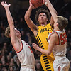 Mankato East's Damani Hayes puts up a shot while being defended by Delano's Max Otto (right) and Calvin Wishart (left) in the first half of Wednesday's state quarterfinal game played at Williams Arena. The Cougars were upset by Delano 79-64. Photo by Jackson Forderer