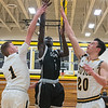 Mankato East's Joich Gong gets a shot up past Hutchinson's Jake Malone (1) and Levi Broersma (20) in the first half of East's victory over the Tigers in the first round of the Section 3AAA boys basketball playoffs. Photo by Jackson Forderer