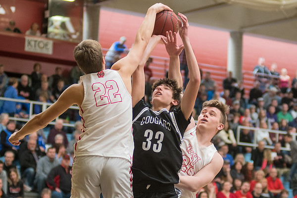 Mankato East's Brandon Schendel (33) has his shot blocked by Mankato West's Spencer Spade (22) and Zach Franke in the second half of play. Photo by Jackson Forderer