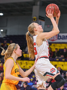 Mankato West's Hailey Kiewiet (right) goes in for a layup after driving past Mankato East's Mackenzie Schweim in a game played at Bresnan Arena in Dec. 2017. Photo by Casey Ek