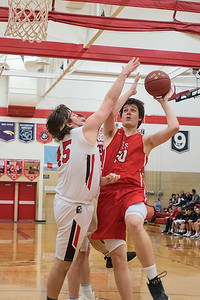 Michael Sathoff of Mankato West (right) goes up for a shot over Worthington's Tyler Linder in the second half of Wednesday's Section 2AAA playoff game. West won 54-38 and will face Mankato East in the next round. Photo by Jackson Forderer