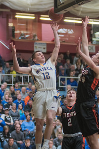 Ryan Default (12) of Waseca puts up a floater over Marshall's Matthew Oaken in the first half of Saturday's Section 3AAA semifinal game. Waseca won the game 78-70 and will face Mankato East in the section championship game. Photo by Jackson Forderer