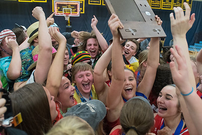 Emily Veroeven holds onto the Section 2AAA girls basketball championship trophy as her teammates were joined by Mankato West students swarming the floor after the Scarlets beat Waseca 47-37 on Thursday. Photo by Jackson Forderer