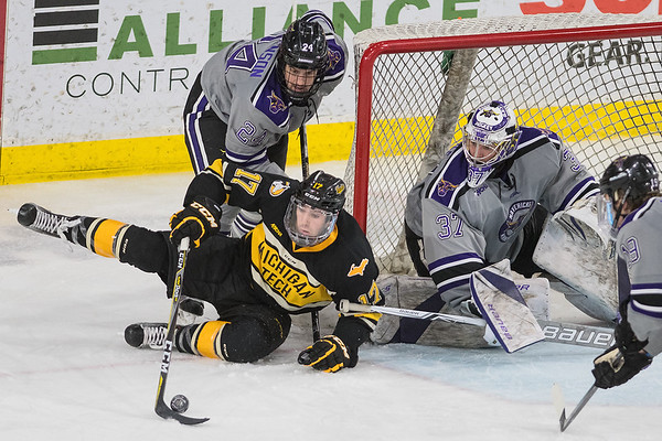 Michigan Tech's Justin Misiak (center) tries to maintain possession of the puck during a wrap-around opportunity while Minnesota State's Edwin Hookenson (top), goalie Connor LaCouvee and Brad McClure defend him. Michigan Tech ramped up the pressure against MSU after getting to within one goal, but the Mavericks held them off for a 2-1 win. Photo by Jackson Forderer