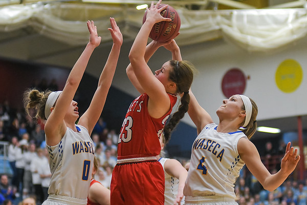 Mankato West's Ashley Gustavson (center) goes up for a shot against Waseca defenders Gus Boyer (left) and Madison Gehloff (right) in the Section 3AAA championship game played in St. Peter. Photo by Jackson Forderer