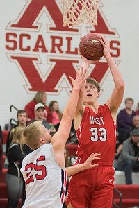Mankato West's Dawson Frericks (33) takes a jump shot over Worthington's Gavin Calmus (25) in the second half of Wednesday's Section 2AAA playoff game. Frericks helped spark the Scarlets' offense to pull away from the Trojans for a 54-38 win. Photo by Jackson Forderer