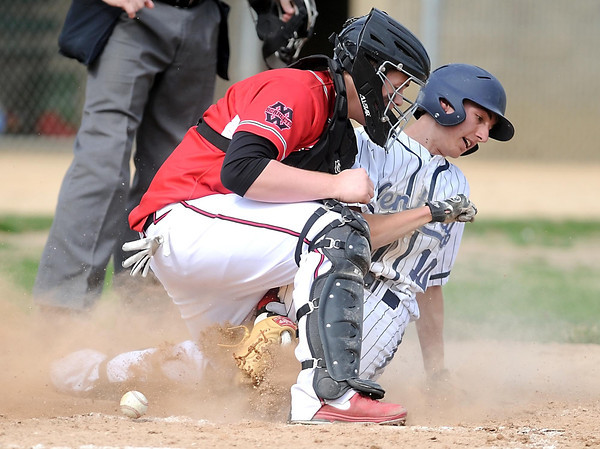 Rochester Century's Jordan Jasik scores after knocking the ball out of Mankato West catcher Conor Wollenzien during the third inning of their first game Tuesday at Franklin Rogers Park.