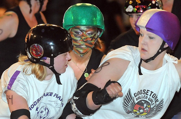M.A.D. Derby Girls' Brutal Army Barbie, back, tries to squeeze between a pair of Moose Lake Mafia blockers during Saturday's roller derby match at the Verizon Wireless Center.