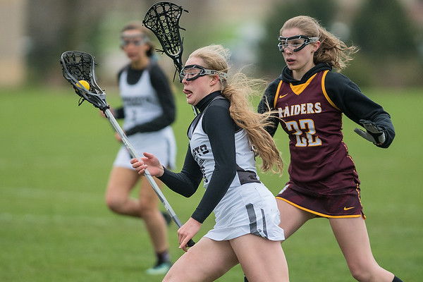 Sydney Kanstrup of Mankato runs past Lauren Weber of Northfield with the ball in Tuesday's lacrosse game played at Dakota Meadows. Photo by Jackson Forderer