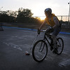 Andy Dowd charges up the rink during a sunset game of bike polo Thursday at the Stoltzman Road rink.