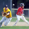 Mankato West baserunner Zack Benzkofer watches to see if Mankato East's Drew Quame catches the ball during the second inning Friday at Wolverton Field. Quame made the catch and threw out Benzkofer at first to complete the double play.