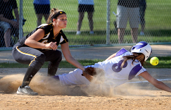 New Ulm's Kristen Forstner slides into third under the tag of Mankato East's Katy Snyder during their game Wednesday at Thomas Park.