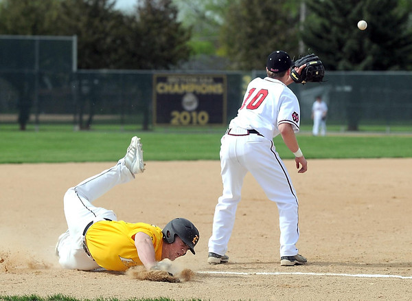 Pat Christman<br /> Mankato East's Drew Quame slides over third base as Mankato West's Josh Athey waits for the throw after Quame's 2-run triple in the second inning Thursday at Wolverton Field.