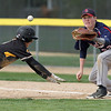 Mankato East's Travis Stockman dives back to first base ahead of the throw to Albert Lea's Parker Mullenbach during the first game of a doubleheader Friday at Wolverton Field. Photo by Pat Christman