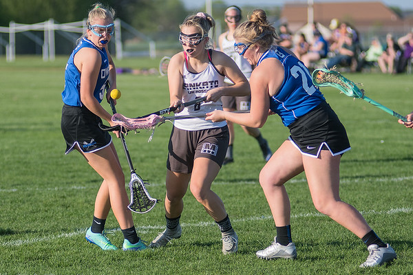 Mankato's Alexis Peterson (center) goes after a loose ball against Owatonna's Taylor Szymanski (left) and Breeze Bergland during Tuesday's game played at Dakota Meadows. Mankato defeated Owatonna 10-8. Photo by Jackson Forderer