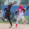 New Prague's Mia Kraimer stretches at first base while Mankato West's Bri Stoltzman reaches the bag during Saturday's game played at Caswell Park. Stoltzman was called safe on the play and the Scarlets won the game 8-2. Photo by Jackson Forderer