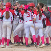 The Mankato West softball team surrounds Kenzie Grunst as she crosses home plate after hitting a home run against New Prague on Saturday. Photo by Jackson Forderer