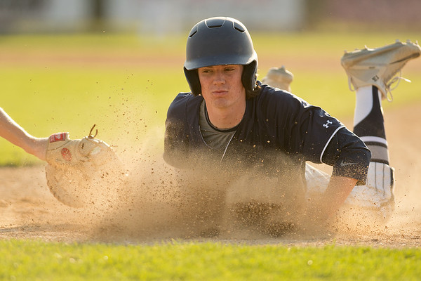 Rochester Century's Jordan Wright slides back to first base in front of a tag by Mankato East's Luke Makovsky. East lost the conference game 13-2. Photo by Jackson Forderer
