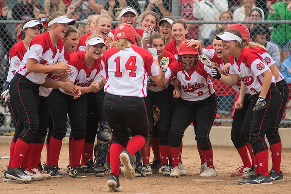 Mankato West's Kenzie Grunst (14) is welcomed to home plate by her Scarlets teammates after hitting a solo home run that capped off an eight-run fifth inning against New Ulm. The Scarlets would go on to win 17-6 and will play Faribault for the Section 2AAA championship. Photo by Jackson Forderer