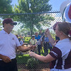 New Ulm Cathedral's head softball coach Bob Mertz (left) gets balloons with the numerals 8-0-0 for his 800th win from player Josie Pautzke after the Greyhounds defeated Sleepy Eye 7-2 on Saturday. Photo by Jackson Forderer