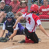 Mankato West's Liz Meidl (4) slides into home plate ahead of a tag from New Ulm catcher Abbey Lee as the Scarlets rallied with two outs in the fifth inning. The Scarlets defeated the Eagles 17-6 to advance in the Section 2AAA softball tournament. Photo by Jackson Forderer