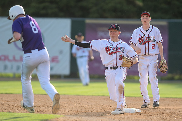 Mankato West's Jaidan Rollings makes the force at second base and throws to first for a double play while New Ulm's Jack Fairbairn tries to get out of the way of the throw during Wednesday's game played at Wolverton Field. Photo by Jackson Forderer