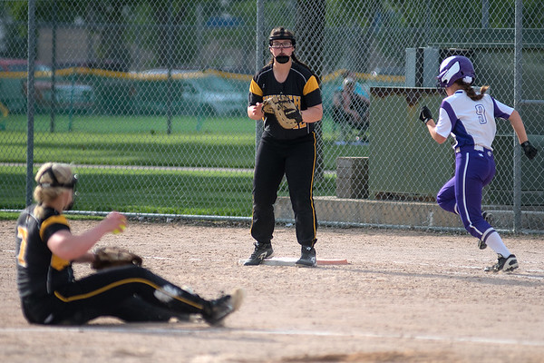 New Ulm's Ashley Mehlhop (right) reaches first safely after Hutchinson's pitcher Grace Penke (left) mishandled a ball hit to her. New Ulm from a 2-0 deficit to win 4-2 over the Tigers in the first round of the Section 2AAA softball tournament played at Caswell Park on Thursday. Photo by Jackson Forderer