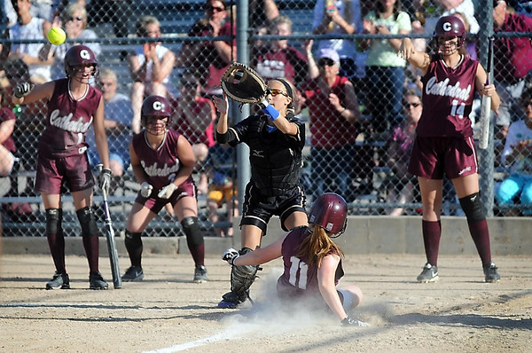 New Ulm Cathedral's Abby Hauser is cheered on by teammates as she beats the throw home to Mankato Loyola catcher Jenna Helget to score in the fourth inning of their Section 2A final Thursday at Caswell Park. Photo by Pat Christman