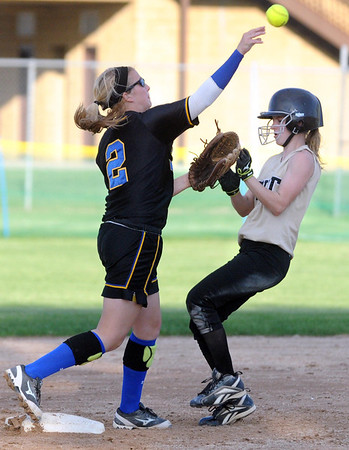 Mankato Loyola's RaeAnn Dose throws over a Lester Prairie/Holy Trinity baserunner while trying to turn a double play during a game Tuesday at Caswell Park.  Photo by Pat Christman